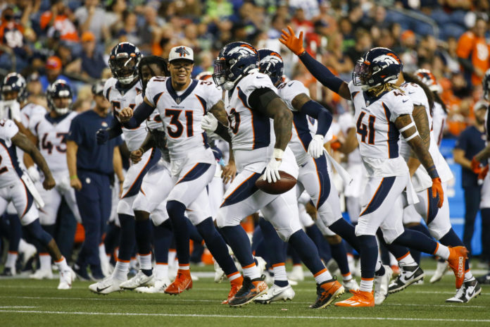 Denver Broncos defensive end DeShawn Williams (90) celebrates with teammates, including safety Jamar Johnson (41) after recovering a fumble against the Seattle Seahawks during the second quarter at Lumen Field.