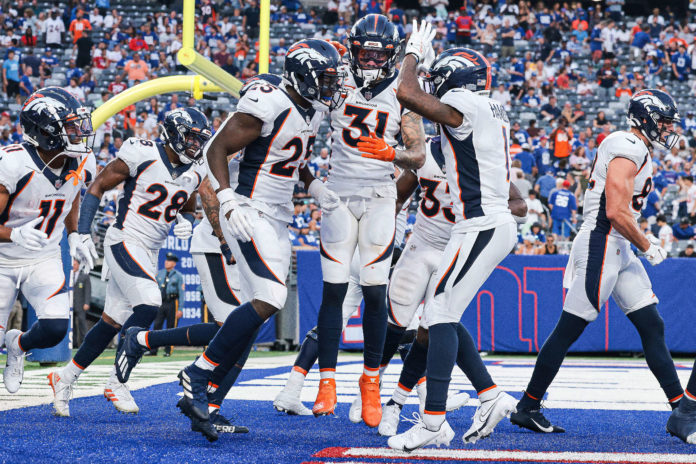 Denver Broncos running back Melvin Gordon (25) celebrates his touchdown with teammates during the second half against the New York Giants at MetLife Stadium.